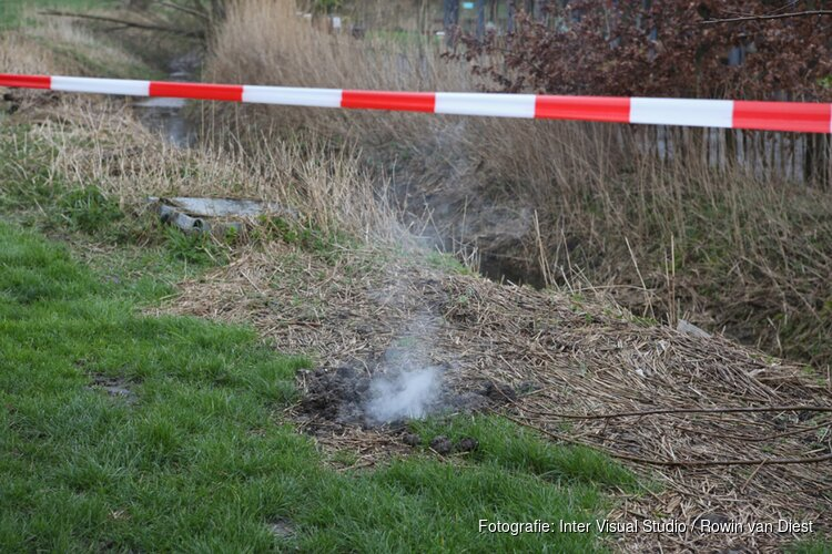 Rook komt uit gras omhoog naast Pannenkoeken paviljoen Cruquius